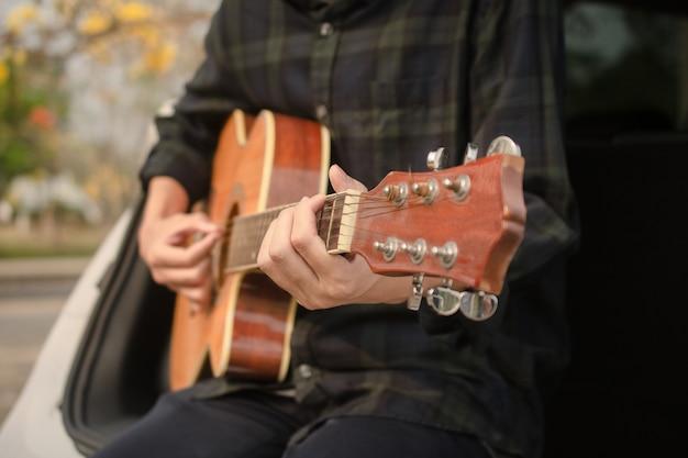 Человек играет на гитаре в машине