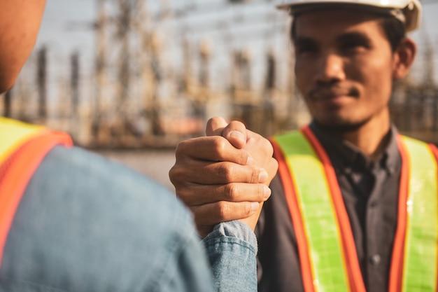 建設現場でのチームワークパートナーシップジェスチャーと人々の概念ハンドシェイクを構築する監督