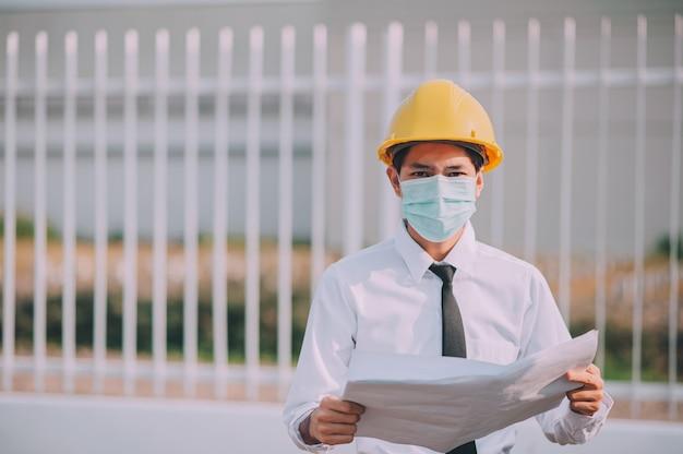 Инженер держит синий фон печати строительной площадки