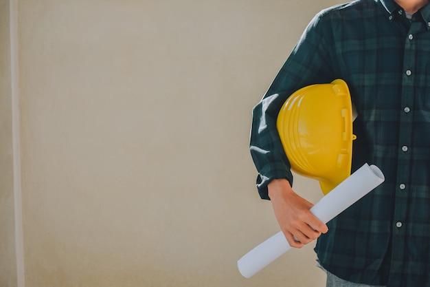 Человек, держащий план каску, руководитель бригадир в строительстве