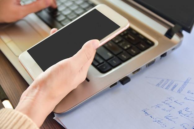 自宅からモバイル作業で呼び出すモバイルスマートフォンを保持している女性