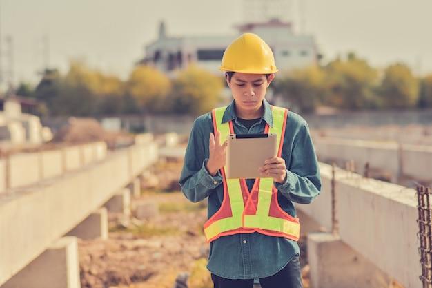 Человек использовать планшет форман защитный костюм желтый шлем безопасности на строительной площадке