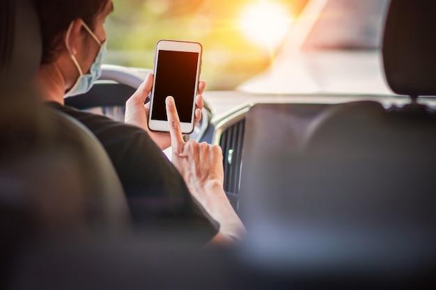 Человек, используя мобильный смартфон в автомобиле