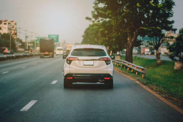 Вождение автомобиля по дороге и небольшое пассажирское автокресло на дороге, используемое для ежедневных поездок