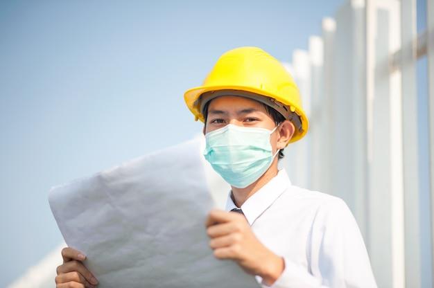 Инженер держит план носить медицинскую маску на строительной площадке
