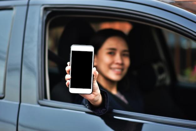 画面上の車のコピー仕様でモバイルスマートフォンを保持する女性