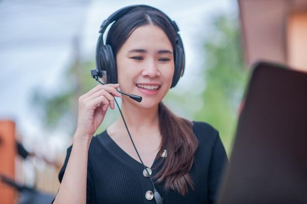 在宅コールセンターサービスで働くフォーカスマイクアジア人女性のサポート、ビジネスワークの新しい通常の相談