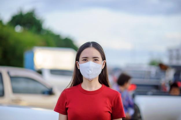 アジアの女性のタイ人はフェイスマスクまたはサージカルマスクを使用してコロナウイルスを保護します。