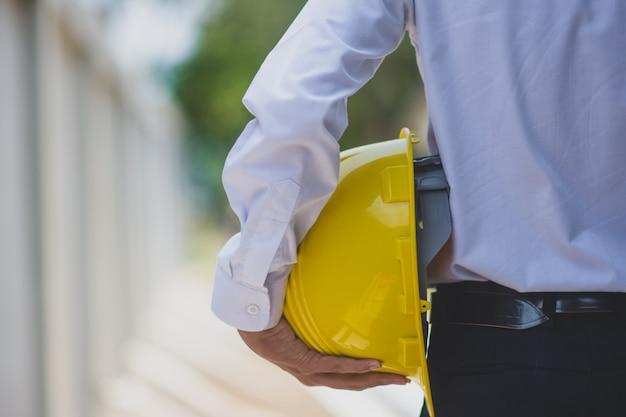 Укомплектуйте личным составом инженер держа здание конструкции работы каски шлема