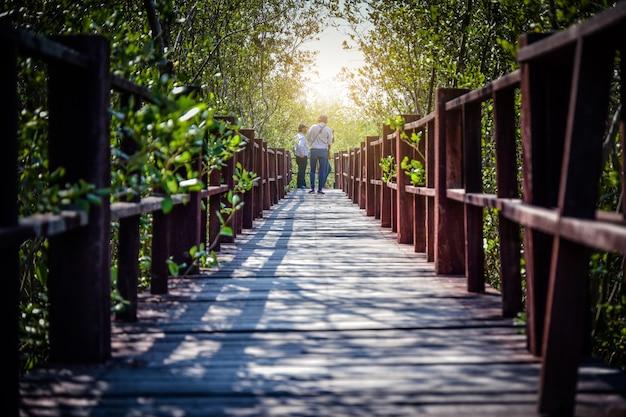 都市公園の木の橋を歩く人々