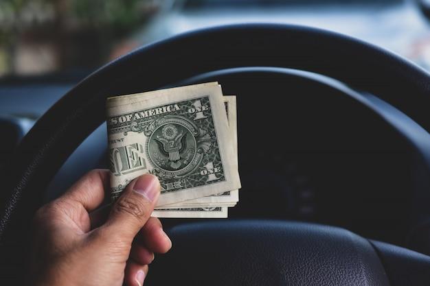 車の中でドルのお金を持っている手