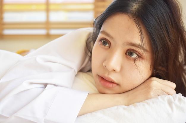 美しい女性は目を覚ますと朝の白いベッドの上