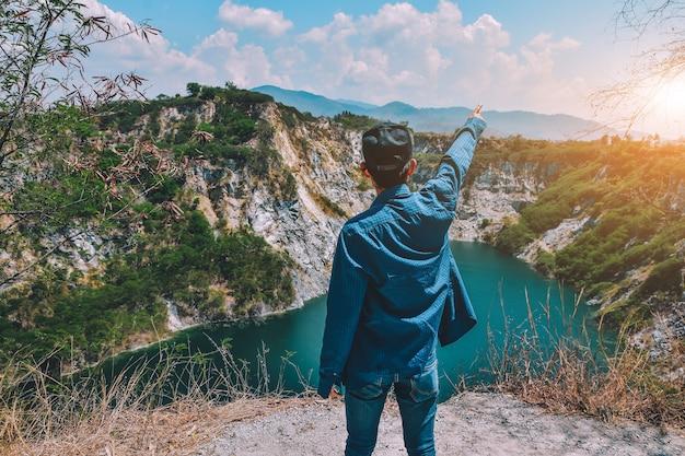 湖の景色で岩の山の上に立っている人