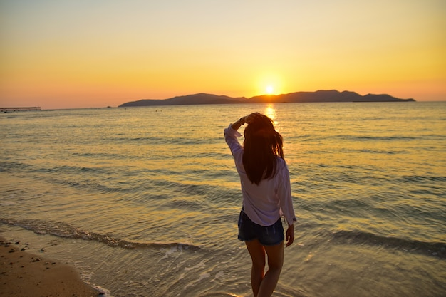 夜の黄金の時間に海の夕日を背景にビーチに立っている女性。