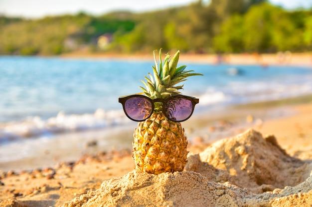 太陽のガラスはビーチシービュー背景でパイナップルです。