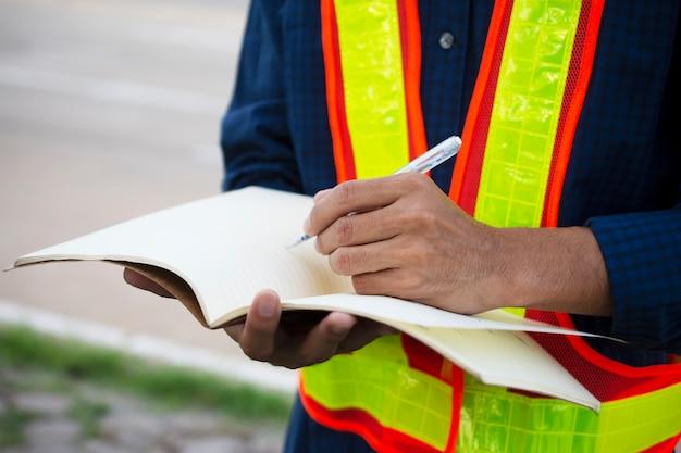エンジニアの書き込みは、プレーニング作業のために本にメモを取る