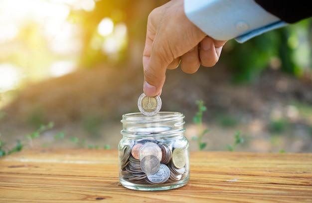 テーブルの上の瓶に入れてコインを持っている手