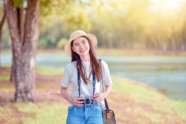 写真カメラのある公園でアジアの女性