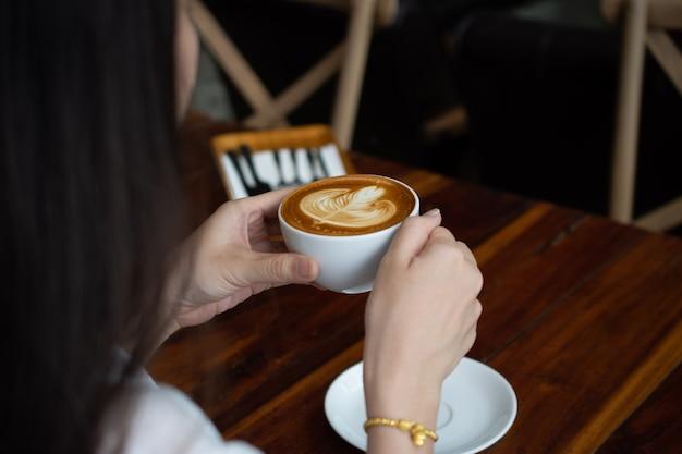 コーヒータイムでの飲み物のためのコーヒーショップに座っている女性
