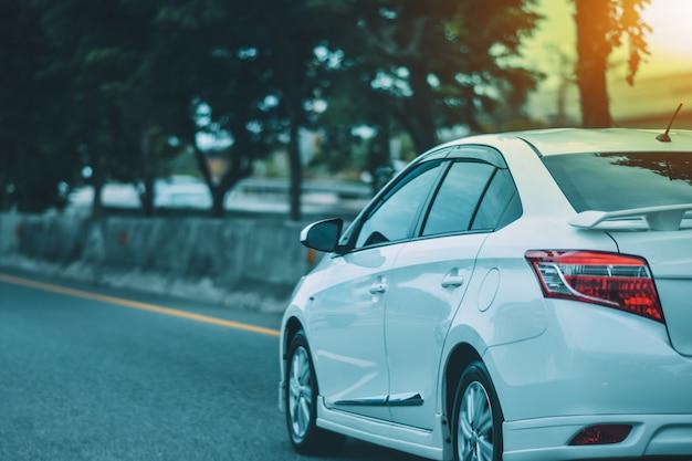 道路に駐車されている車と、毎日の旅行に使用される道路上の小さな乗用車の座席