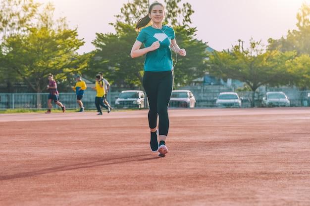 Бегун женщины бегают трусцой или бегают вечером на солнце
