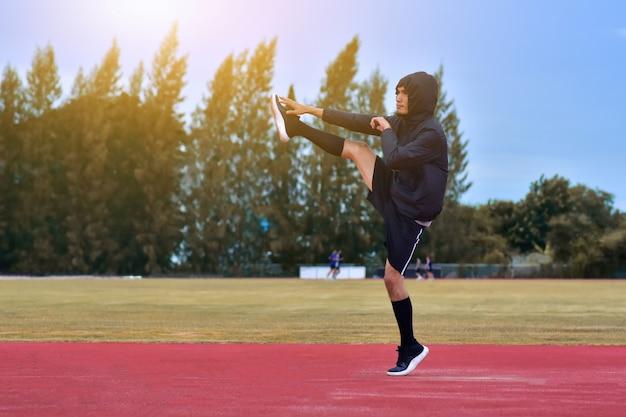 ランナーの男は、実行またはジョギングの前に体をワームします。