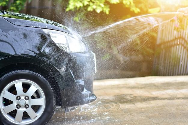 自宅の日光で車を掃除する人