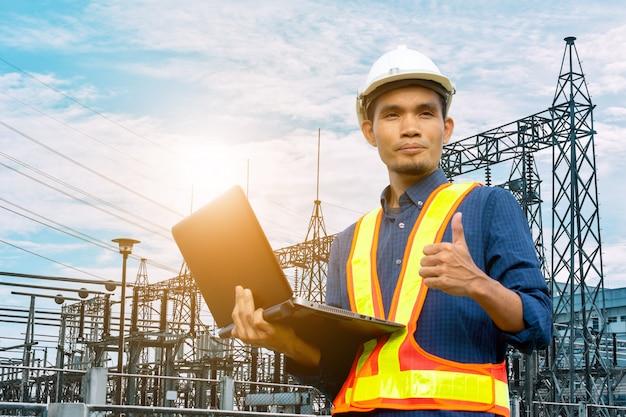Инженер держит компьютер ноутбук электрический завод системы