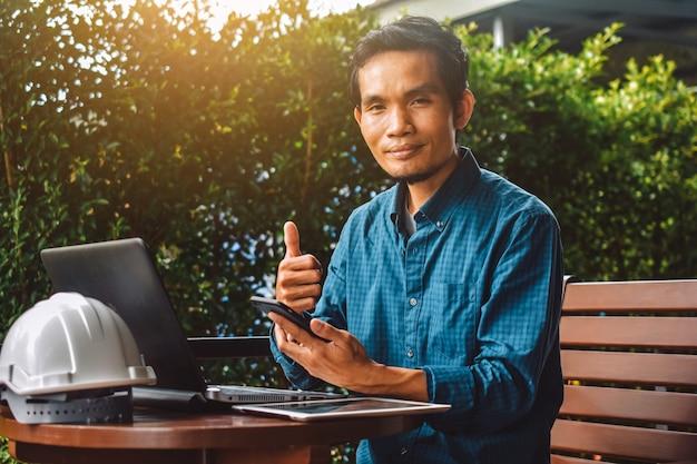 Человек используя компьтер-книжку умного телефона работая малый бизнес