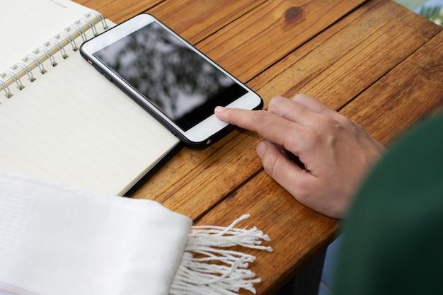 Касание руки на экране мобильный смартфон за деревянным столом