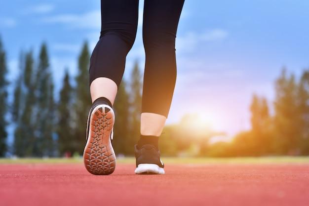 ランナーの女性は運動スポーティな朝の日差しを実行しています