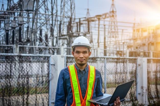 Инженер держит компьютер ноутбук высоковольтной электростанции