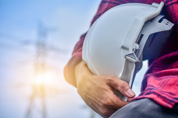 ハード帽子人マネージャーサービス高電圧発電所の背景を保持しているエンジニア