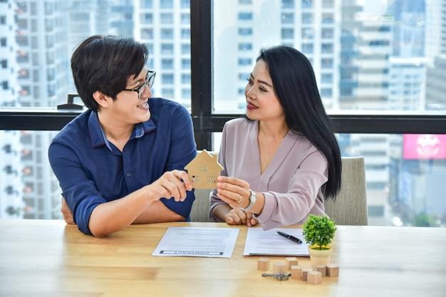 Крупным планом дома модель пара покупает дом для семьи
