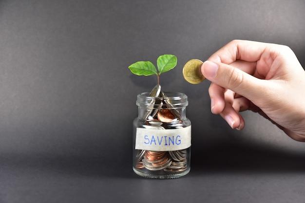 お金ビジネス金融投資成長コンセプトを節約瓶ガラスの手コイン