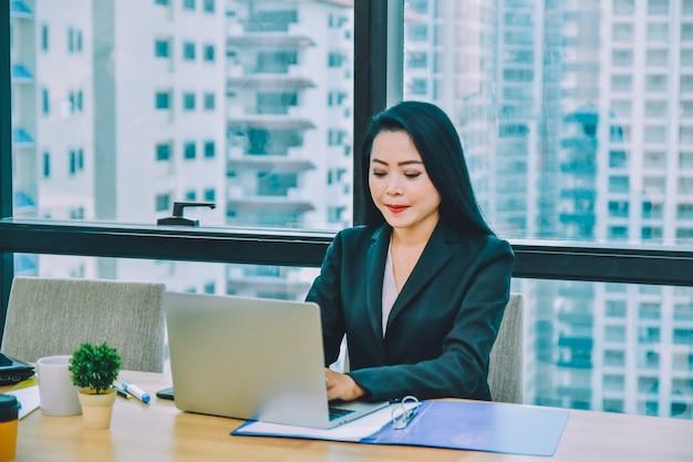 オフィスのデスクで働くラップトップコンピューターノートを使用してアジアの実業家