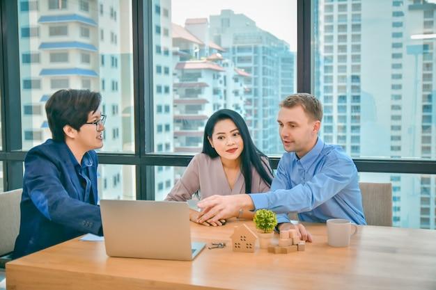 Муж и жена обсуждают с продавцом жилой кондоминиум. консультация покупка дома и резиденции.