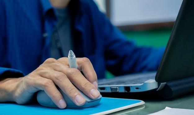 ペンを押しながら仕事でコンピューターノートパソコンのマウスコントロールを使用しての実業家