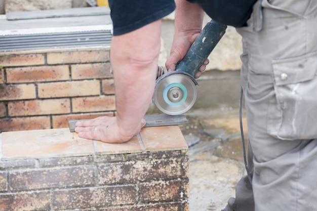 グラインダーでタイルを切る瓦職人