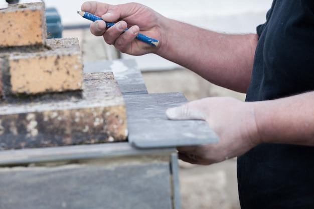 Плиточник измеряет и ставит отметки, чтобы разрезать и уложить плитку