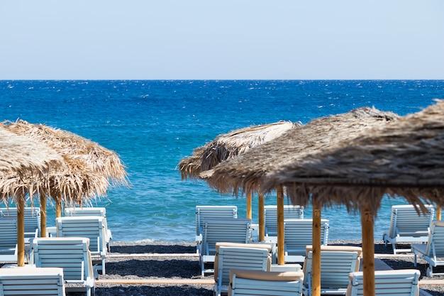 サントリーニ島の海沿いのパラソルとデッキチェアのあるビーチ