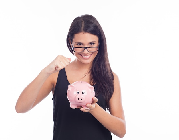 Молодая женщина в очках счастлива с копилкой