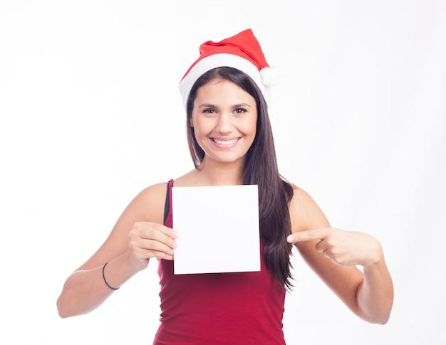 空白のカードまたはメモを示すサンタ女性