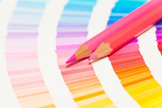 Красные и розовые цветные карандаши и таблица цветов всех цветов