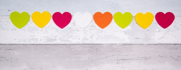 Красочные чувствовал сердца на фоне старых деревянных планок, напоминающих старый паркетный пол. концепция дня святого валентина и любви в целом