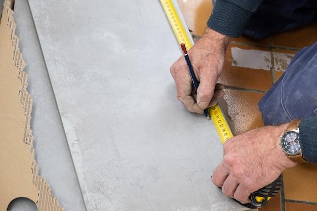 タイラーは、タイルを切断する前に測定します