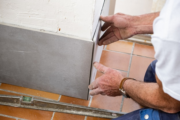Плиточник кладет керамическую плитку на стену