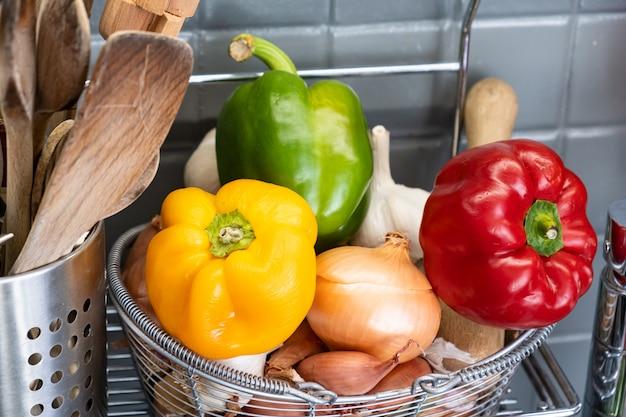Маленькая корзинка на кухне рядом с посудой с чесноком, луком, луком-шалотом и красным желтым и зеленым перцем