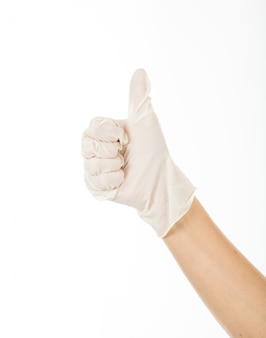 ラテックスグローブで成功を示すために親指を立てる。女性の右手はいい考えです。