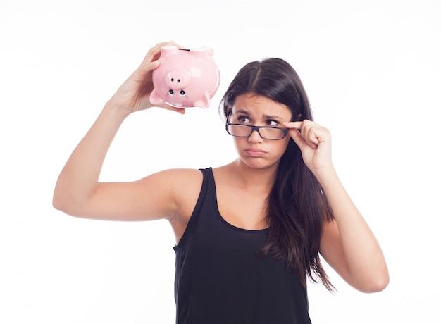 貯金箱を心配している若い女性